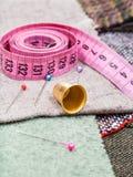 Bande de mesure rose, goupilles, dé sur le tissu Photographie stock libre de droits