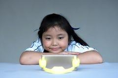 Bande dessinée de observation de petite fille sur le périphérique mobile Photos stock