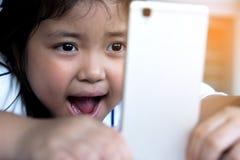 Bande dessinée de observation de petite fille sur le périphérique mobile Images stock