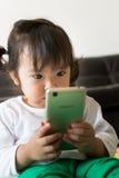 Bande dessinée de observation de petite fille sur le périphérique mobile Photographie stock
