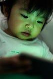 Bande dessinée de observation de petite fille sur le périphérique mobile Photographie stock libre de droits