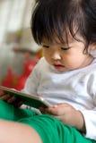 Bande dessinée de observation de petite fille sur le périphérique mobile Photo stock