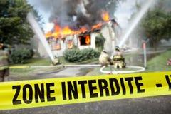 Bande française d'Interdite de zone avec des sapeurs-pompiers et une maison brûlante Photographie stock libre de droits