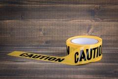bande jaune de précaution sur un fond en bois Glissière de sécurité pour la barricade de police, pour des entrepreneurs photos libres de droits