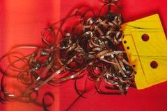Bande magnétique pour enregistrement sonore jaune avec le film sur un fond rouge, configuration d'appartement de vue supérieure C photographie stock