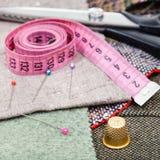 Bande rose de mesure, goupilles, dé, cisaillements sur le tissu Photo stock