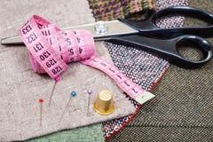 Bande rose de mesure, goupilles, dé, cisaillements sur le tissu Photos stock