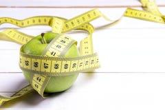 Bande verte de centimètre de pomme et de jaune sur le backgroun en bois blanc Photo stock