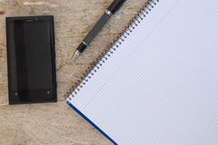 Banded notebook, cell phone and pen on a wooden table with copys Stock Image