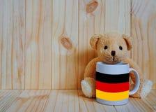 Bandeira alemão em um copo de café com urso de peluche e fundo de madeira Fotos de Stock
