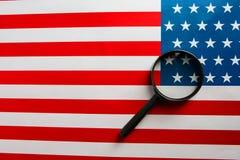 A bandeira americana é vista através de uma lupa Espiões e conceito dos EUA da fiscalização Controle do estado de unido imagens de stock