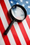 A bandeira americana é vista através de uma lupa Espiões e conceito dos EUA da fiscalização Controle do estado de unido fotografia de stock