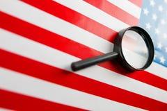A bandeira americana é vista através de uma lupa Espiões e conceito dos EUA da fiscalização Controle do estado de unido imagem de stock