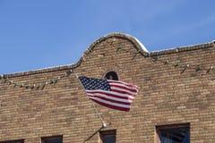 A bandeira americana acena da fachada do sudoeste retro da construção de tijolo do estilo pendurada com luzes do partido imagem de stock