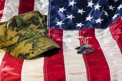 Bandeira americana com as etiquetas da tampa e de cão das forças armadas Fotos de Stock