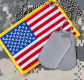 Bandeira americana com as etiquetas de cão na camuflagem Fotos de Stock