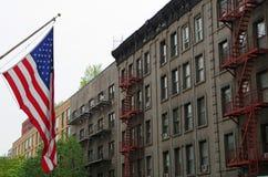 Bandeira americana com fundo das construções do nyc Fotos de Stock