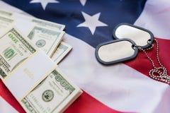 Bandeira americana, dinheiro do dólar e crachás militares Foto de Stock