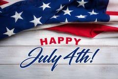 Bandeira americana em um fundo de madeira vestido branco com cumprimento do 4 de julho Fotos de Stock Royalty Free