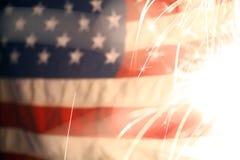 A bandeira americana iluminou-se acima por chuveirinhos para 4ns de celebrações de julho Imagens de Stock