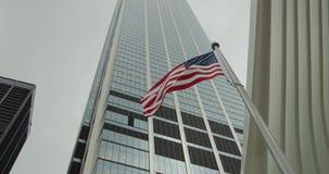 A bandeira americana na perspectiva dos arranha-céus retarda a ondulação Midle disparou da bandeira do ESTADOS UNIDOS EUA filme