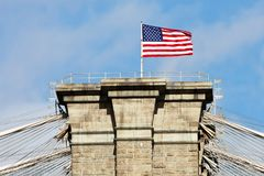 Bandeira americana na ponte de Brooklyn superior Fotografia de Stock Royalty Free