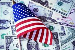 Bandeira americana no fundo das notas de dólar dos E.U. Pena, eyeglasses e gráficos Imagem de Stock Royalty Free