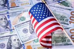Bandeira americana no fundo das notas de dólar dos E.U. Pena, eyeglasses e gráficos Fotografia de Stock Royalty Free