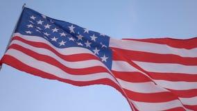 Bandeira americana no vento no céu azul, movimento lento video estoque