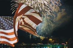 A bandeira americana que acena em fogos-de-artifício amarelos verdes vermelhos efervescentes da celebração sobre o céu estrelado  Imagem de Stock
