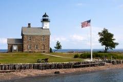 Bandeira americana que voa perto do farol de pedra em Connecticut fotografia de stock royalty free