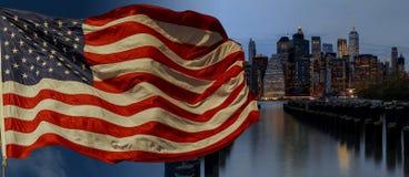Bandeira americana que voa uma noite da skyline das construções de New York City manhattan da skyline tomada Foto de Stock