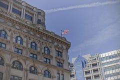A bandeira americana voa orgulhosamente sobre a cidade Fotografia de Stock