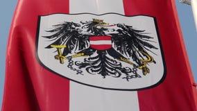 Bandeira austríaca com emblema nacional, símbolo que acena lentamente no vento vídeos de arquivo