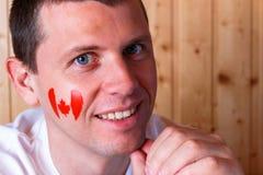 Bandeira canadense na cara do homem novo Foto de Stock