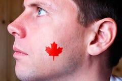 Bandeira canadense na cara do homem novo Imagens de Stock