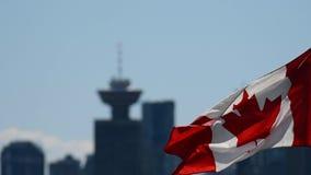 A bandeira canadense que acena no céu, com uma torre fora-focalizada do porto no fundo