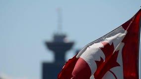 A bandeira canadense que acena no c?u, com uma torre fora-focalizada do porto no fundo