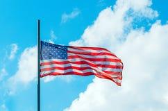 Bandeira colorida de ondulação dos EUA do americano no céu azul Imagens de Stock