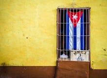 A bandeira cubana em uma janela Fotografia de Stock Royalty Free