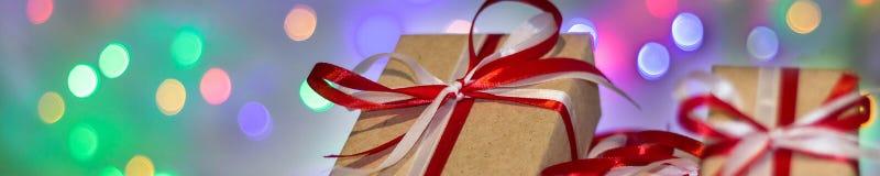 Bandeira da caixa de presente do Natal contra o fundo do bokeh Cartão do feriado fotografia de stock royalty free