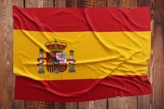 Bandeira da Espanha em um fundo de madeira da tabela Opini?o superior enrugada da bandeira espanhola fotografia de stock royalty free