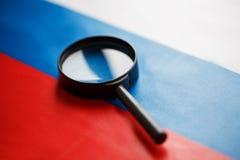 A bandeira da Federação Russa é vista através de uma lupa Espiando e monitorando Rússia Monitorando o estado de fotos de stock royalty free