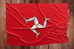 Bandeira da ilha do homem em um fundo de madeira da tabela Opini?o superior enrugada da bandeira fotografia de stock royalty free