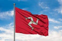 Bandeira da ilha do homem que acena no vento contra o céu azul nebuloso branco imagem de stock royalty free
