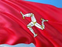 Bandeira da ilha do homem que acena no vento contra o c?u azul profundo Tela de alta qualidade imagem de stock royalty free
