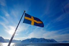 Bandeira da Suécia com céu azul Ilha rochosa com neve Montanha nevado branca, crepúsculo azul do iceberg da geleira, oceano Nuven Imagens de Stock Royalty Free