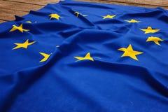 Bandeira da Uni?o Europeia em um fundo de madeira da mesa Opini?o superior da bandeira de seda da UE foto de stock royalty free