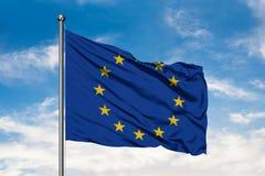 Bandeira da União Europeia que acena no vento contra o céu azul nebuloso branco foto de stock royalty free