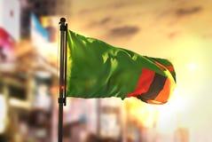 Bandeira da Zâmbia contra o fundo borrado cidade no luminoso do nascer do sol Imagens de Stock